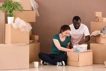 Interracial couple unpacking boxes indoors. Moving into new house