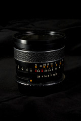 Photographer DSLR wide fixed focal length lens. Dark styled photo. Camera lens with focus ring.