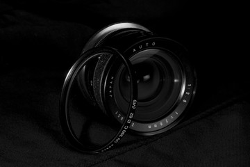 Vintage wide DSLR lens aperture close up with UV filter.