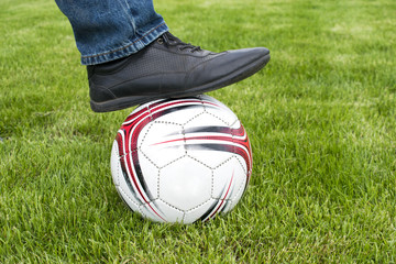 foot on a soccer ball on a background of a green field