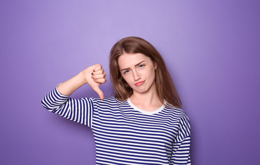 Beautiful young woman showing thumb-down gesture on color background