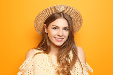 Beautiful young woman with hat on color background