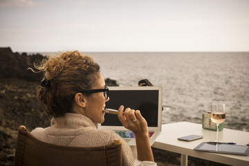 Nice lifestyla for nbeautiful caucasian woman working in alternative office place. outdoor in front of the ocean. digital nomad and internet work for modern possibilities and freedom from closed