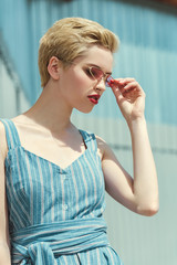 girl with short hair posing in trendy blue dress and pink sunglasses
