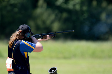 Teenage girl shooting in a shotgun competition.