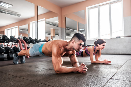 sporty couple doing plank exercise i the gym