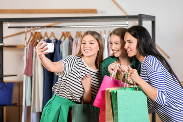 Young pretty women taking selfie with shopping bags in clothing shop