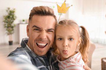 Happy father and daughter taking funny selfie at home