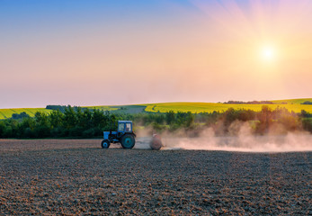 the tractor pulls the plow in the field on sunset
