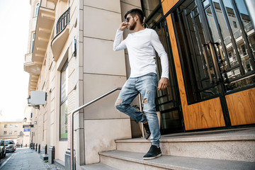 A young man travels through the streets of the city. Boy in sunglasses Stylish man near the building. The man sits on a whip. Beard and hair in a stylish guy.