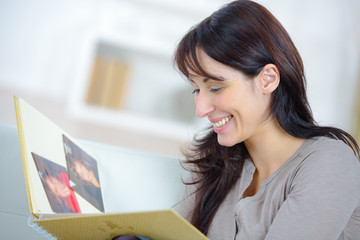 woman looking at photo album in her apartment