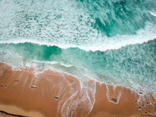 Aerial view of sandy beach with waves perfect spot for surfing. Drone photo