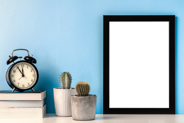 Black mockup frame with two cactuses in gray pots, black alarm clock and books on a blue background