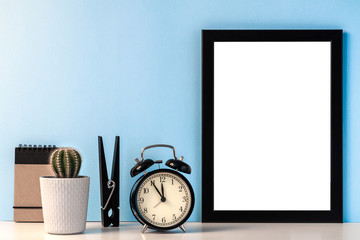 Black mockup frame with cactus in a gray flower pot, black alarm clock, notebook and oversize clip on a blue background