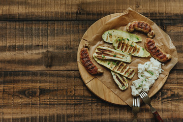 Assorted grilled zucchini and fried sausages with fresh cheese and thyme on a rustic background. Nearby there are cutlery.