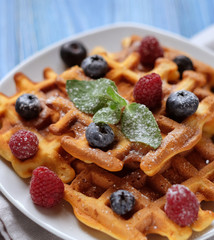 Traditional belgian waffles with fresh berrys and sugar powder on white plate, blue wooden background.