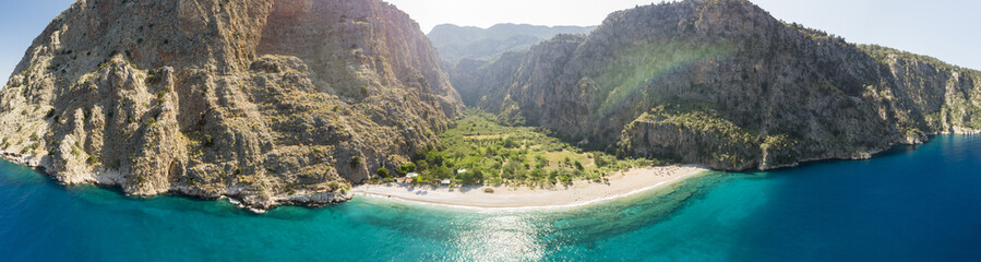 Remote beach from the air surrounded by a steep sided valley and turquoise water with sailing ship, Oludeniz, Turkey panoramic