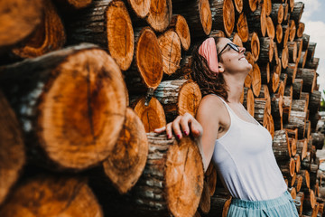 .Young and pretty tourist enjoying a day around Bali, Indonesia. Relaxed, free and happy gesture on a colorful background of wooden logs. Lifestyle