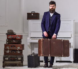 Macho elegant on strict face stands near pile of vintage suitcase, holds suitcase. Man, traveller with beard and mustache with luggage, luxury white interior background. Baggage delivery concept.