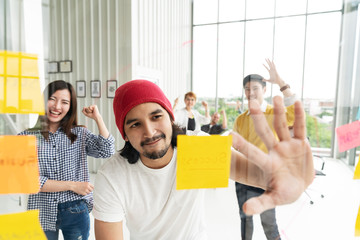 Group of young successful creative multiethnic team smiling and brainstorm together in modern office. Man and woman happy looking at sticky post note on glass wall sharing idea with engaged cheerful.