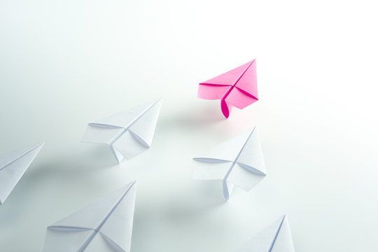 Woman leadership concept with pink paper plane leading among white.