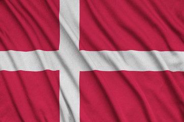 Denmark flag  is depicted on a sports cloth fabric with many folds. Sport team banner