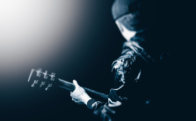 back of asian male musician playing guitar on stage