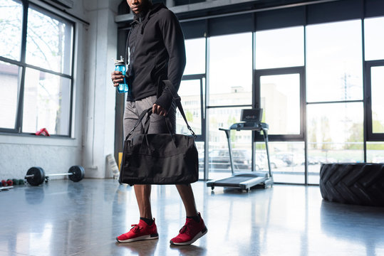 cropped shot of african american man in sportswear holding bag and bottle of water in gym