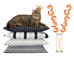 The cat in the gold crown lies on pile of pillows near a glass vase with shrimp skewers. White background
