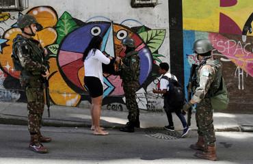 A Brazilian navy soldier checks a resident at Chapeu Mangueira slum in Rio de Janeiro
