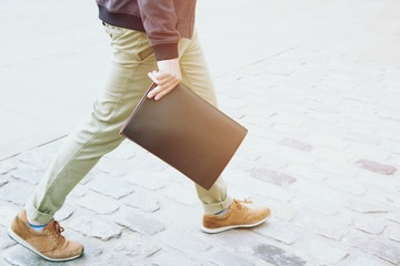 close up business man in Casual wear. hand holding briefcase Document bag walking street on the road.