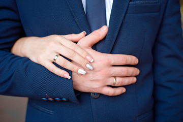 Close-up Bride and groom's hands with wedding rings. Groom putting golden ring on finger. Love and marriage.