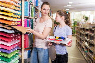 Young mother with daughter choosing school accessories in store