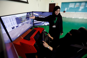 A driving instructor teaches a trainee on a simulator car during a driving lesson at Saudi Driving Center in Riyadh