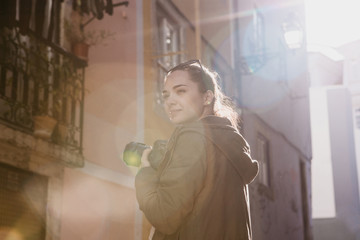 A street photographer or a young woman takes pictures of authentic houses in Lisbon in Portugal. A professional photographer or tourist taking pictures for memory