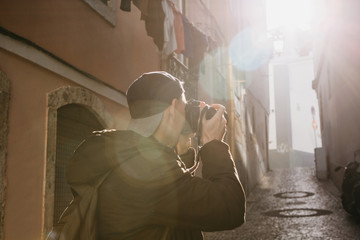 A street photographer or a young man takes pictures of authentic houses in Lisbon in Portugal. A professional photographer or tourist taking pictures for memory