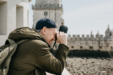 A professional photographer or a young male tourist photographes the sights in Lisbon in Portugal. Leans the camera to his head and laughs. Very satisfied with the photo