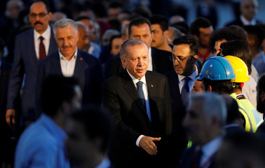 Turkey's President Tayyip Erdogan greets workers as he arrives to the Istanbul's third international airport which is still under construction during a ceremony marking the first landing