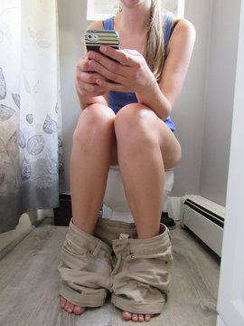 Woman sitting on the toilet while using her cell phone with pants around her ankles