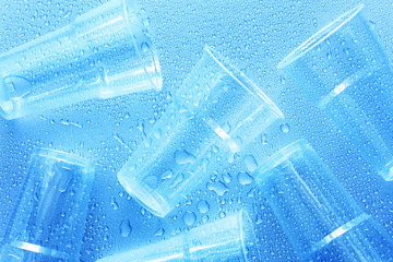 Disposable plastic cup with water drops on a blue background