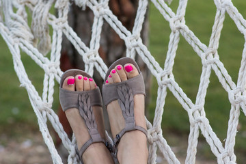 Woman relaxing in the hammock at the garden with beautiful pedicure