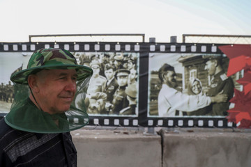A man wears a mosquito head net as he stands next to World War II era pictures in the bank of Volga river in Volgograd