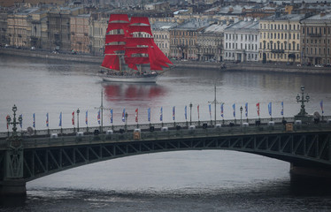 Sweden's brig Tre Kronor with scarlet sails floats on the Neva River behind Troitsky bridge during a rehearsal for the festivities marking school graduation in St. Petersburg