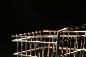 Close up of a small shopping cart on a black background. Silver metal shopping cart shot with macro lens shallow depth of field. Shopping and commerce concept.