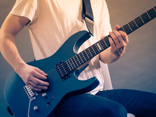 Close up of man playing on electric guitar