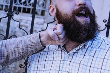 Aggression and Pain Concept. Portrait of bearded hipster man takes a punch in the face.