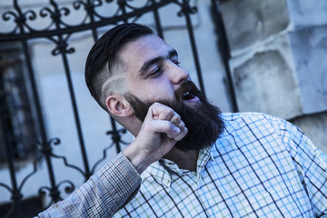 Portrait of bearded hipster man takes a punch in the face.