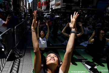 People participate in a yoga class during an annual Solstice event in the Times Square in New York