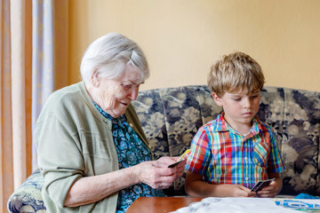 Active little preschool kid boy and grand grandmother playing card game together at home