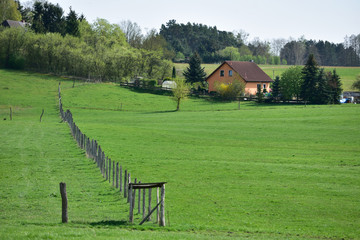 A small country house with a field and a farm.